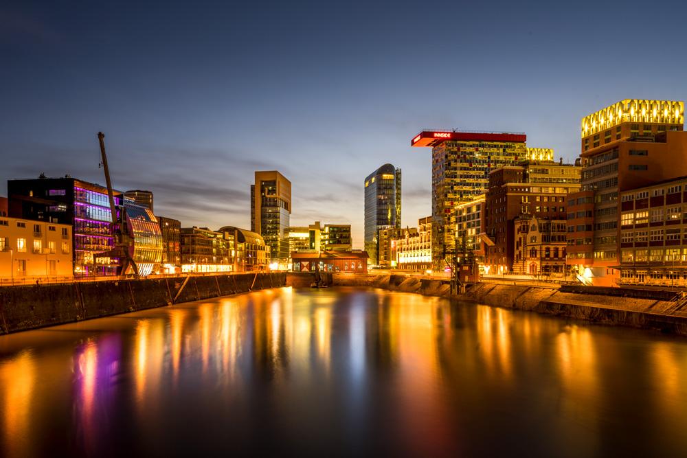 Hafenbecken und Gebäude mit Lichtreflektionen auf dem Wasser zur Abenddämmerung