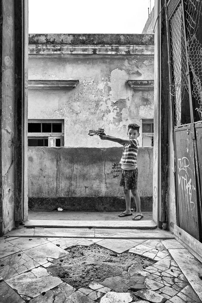 Kind auf Balkon in Havanna spielt mit Spielzeugpistole